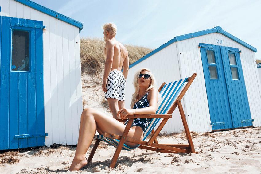 Daily Paper x Ace & Tate — dámské plavky – jednodílné, tmavě modré s bílými křížky, sluneční brýle; pánské koupací šortky, bílé plavky s tmavě modrými křížky