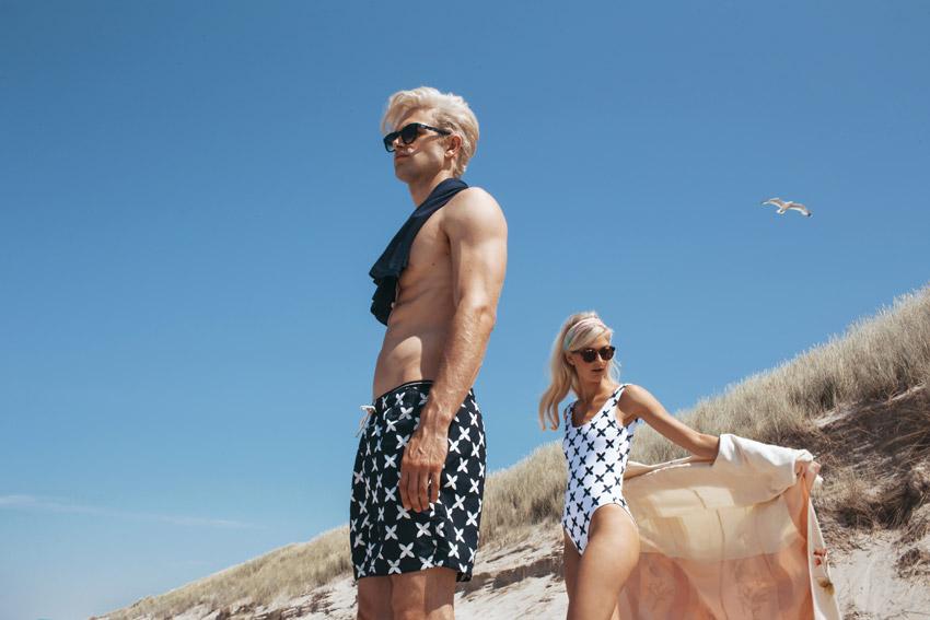 Daily Paper x Ace & Tate — pánské koupací šortky, tmavě modré plavky s bílými křížky, bílé dámské plavky – jednodílné, s bílými křížky; sluneční brýle