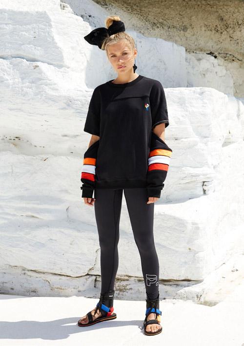 P.E Nation — černá sportovní mikina, oranžové a bílé pruhy na rukávech — černé legíny — pantofle s řemínky — dámské sportovní oblečení