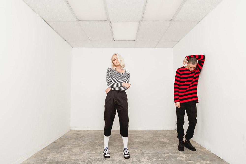 Publish — dámské černo-bílé pruhované tričko — černé tříčtvrteční kalhoty — pánské černo-červené tričko s pruhy — černé kalhoty joggers — His and Hers — lookbook — pánské oblečení, dámské oblečení