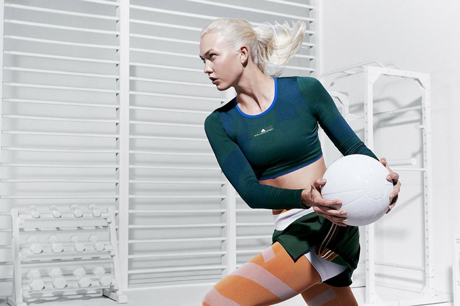 adidas x Stella McCartney — zelený dámský top pod prsa s dlouhým rukávem — zelené šortky — oranžové legíny — sportovní oblečení — jaro/léto 2018