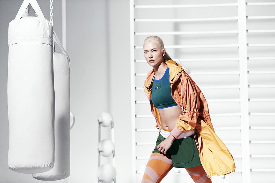 adidas x Stella McCartney — dámská dlouhá sportovní parka s ombre efektem s kapucí, oranžovo-žlutá — dámské zelené šortky — zelená podprsenka/top — sportovní oblečení — jaro/léto 2018
