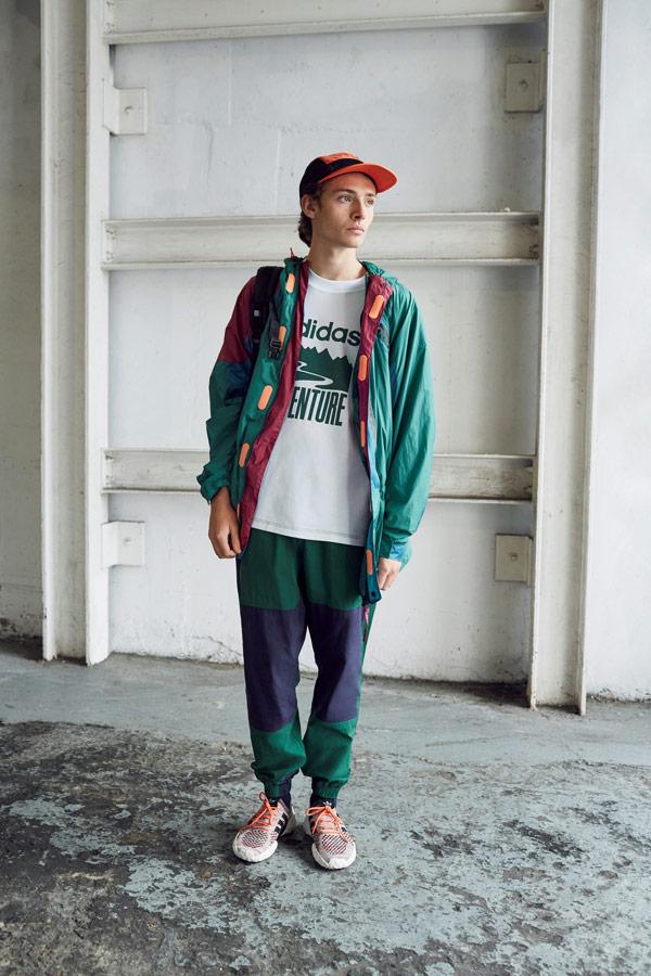 adidas Originals Atric Pack — oblečení — šusťáková zelená bunda s kapucí — bílé tričko s potiskem — modro-zelené šusťákové tepláky — boty F/22 Primeknit — oranžová kšiltovka