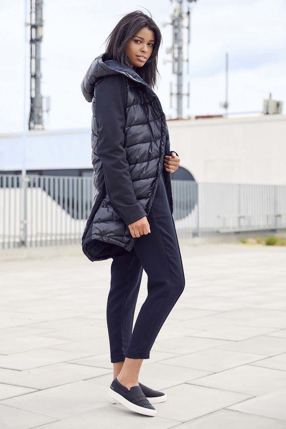 Bench — dlouhá dámská prošívaná bunda s kapucí — tmavě modré kalhoty nad kotníky — modré slip-on tenisky