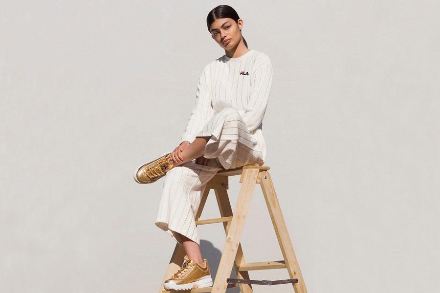 Fila — dámská bílá mikina s proužky — dámské bílé široké kalhoty s proužky — zlaté boty — sportovní oblečení — lookbook — jaro/léto 2018