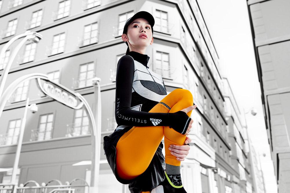 adidas by Stella McCartney — oranžové legíny — šedo-černé teplé tričko s dlouhým rukávem — funkční sportovní oblečení — podzim/zima 2018