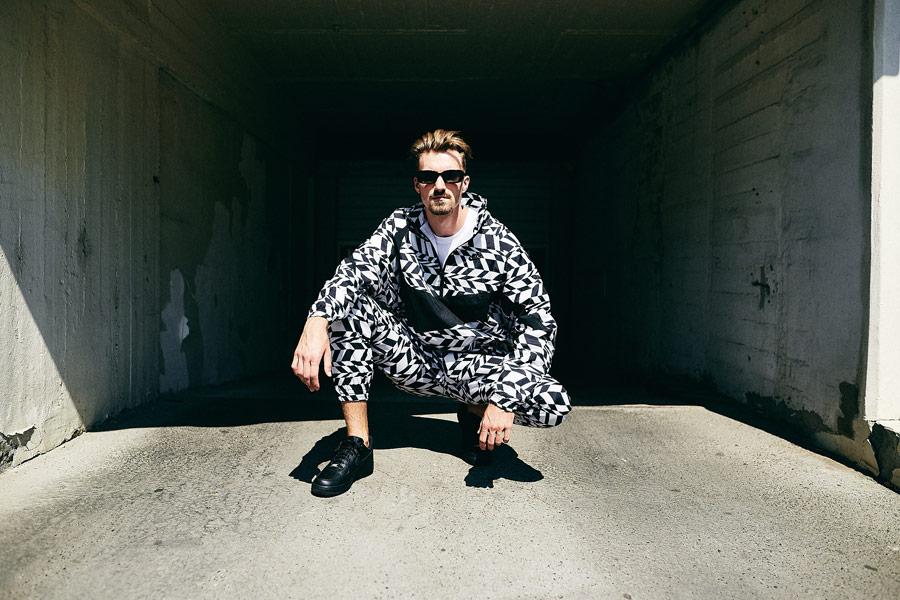 Nike x Queens lookbook — bílo-černá vzorovaná sportovní bunda s kapucí — bílo-černé kalhoty joggers se vzorem — černé boty Nike Air Force 1 Low