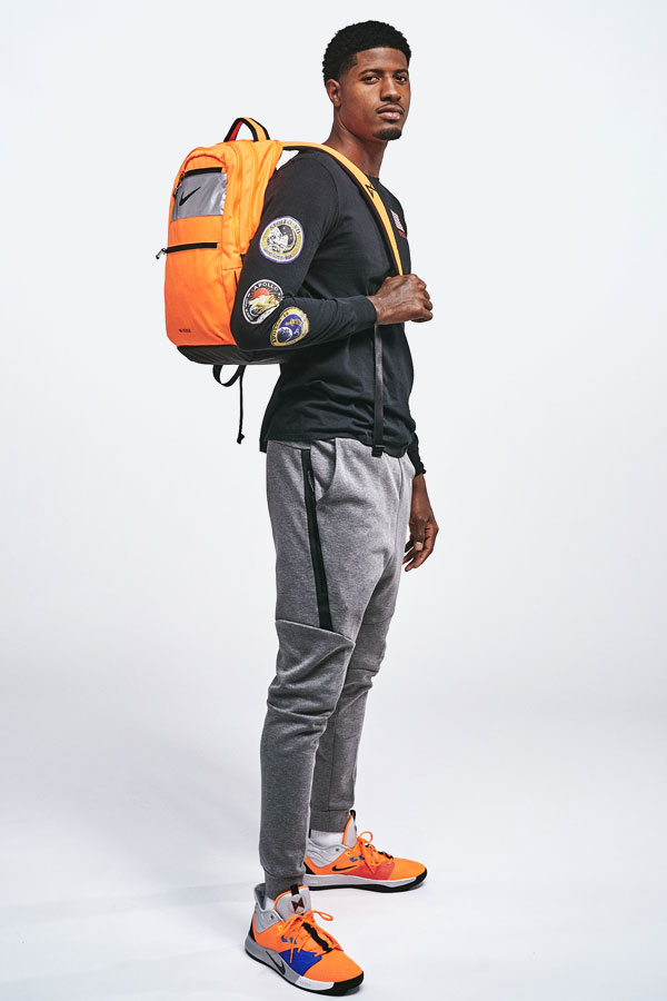 Nike PG3 — Paul George — oranžový batoh — černé tričko s nášivkami — šedé tepláky — oranžové boty PG3 — NASA