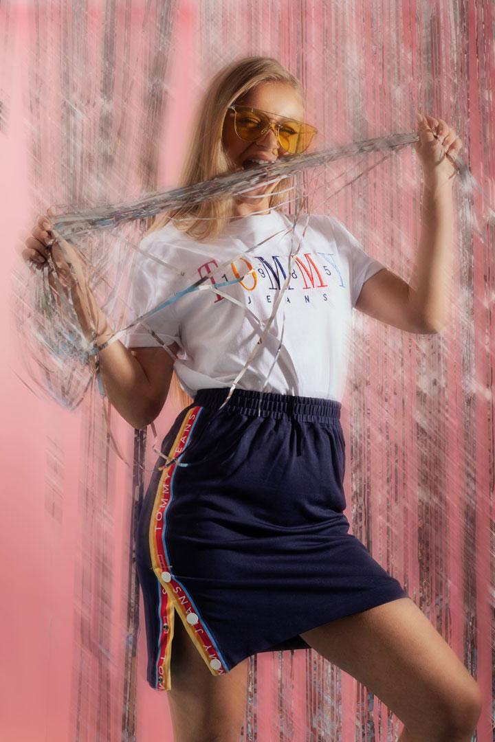 Tommy Jeans x Queens — lookbook — dámské bílé tričko s potiskem — letní modrá sukně